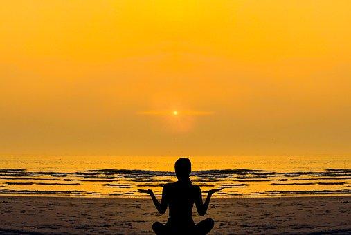 夕焼けの中のビーチヨガのイメージ画像